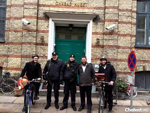 Rabbi Yitzchok Loewenthal, co-director of Chabad of Denmark in Copenhagen with his wife, Rochel, in front of the Chabad House last month with volunteers who were handing out boxes of shmurah matzah by bike for Passover and with security officers who now guard Jewish institutions there.