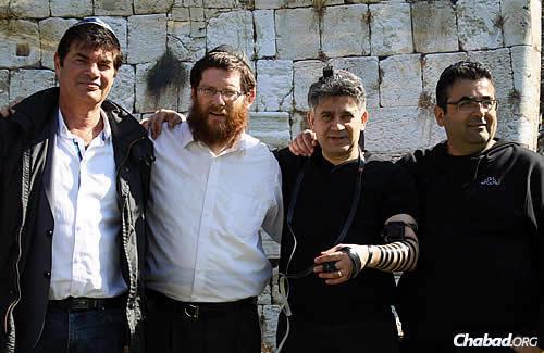 Men wrap tefillin with the rabbi in front of a replica of the Western Wall in Jerusalem (the Kotel), which is set up in the park for Lag BaOmer.