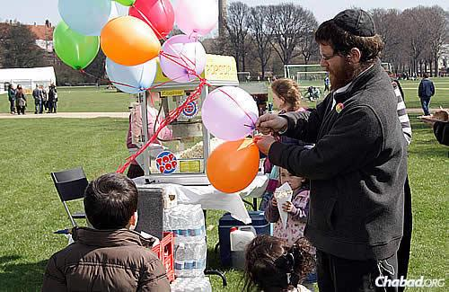 The rabbi hands out balloons, and the children dig into bags of popcorn, part of a carnival feel.