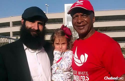 The author, Rabbi Menachem Posner, and one of his daughters take time for a photo with Jesse White.