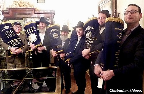Rabbi Bentzion Chanowitz, second from left, along with those involved in the project display the refurbished Torahs before they are sent on loan to their new homes.