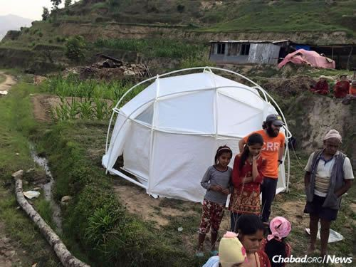 A family with their new shelter. (Photo: Chabad of Nepal)
