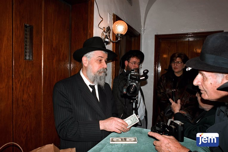 """With the photographer and others at the Rebbe's """"dollars"""" distribution spot on 26 Cheshvan, 5752."""