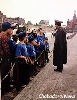 In an unprecedented show of Jewish pride mere steps from the Kremlin, Camp Gan Israel held a traditional lineup on Red Square in 1991. Rabbi Dan Rodkin, center, a Moscow native who had recently become religious, explains what they're doing there to a once-feared Soviet officer.