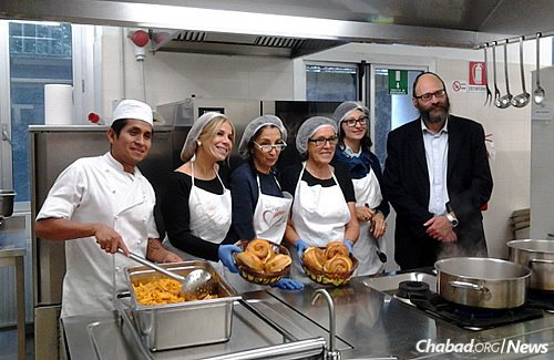 Meals are provided in Milan, Italy, to Eritrean, Ethiopian, Sudanese and Syrian refugees, many of them Muslim, who temporarily stay in rooms below the Milan central train station, these days retrofitted as a Holocaust memorial and museum. Some of the cooking staff and volunteers, shown with Rabbi Igal Hazan, who oversees the kitchen.