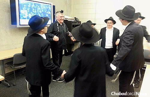 The group celebrated with singing and dancing. Days later, Winthrop, 88, attended the boys' school graduation ceremony, putting tefillin on again, this time with Raices' father, Rabbi Sholom Ber Raices of Lubavitch Chabad of Skokie.