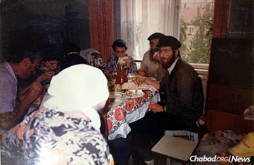 """Rabbi Levi Heber, right, then 19, at the Moscow apartment where Genin performed circumcisions. The apartment belonged to an elderly woman known as Bubbe Charne, who would prepare a celebratory """"feast"""" following each brit performed at her apartment. Genin can be seen partially obscured by Heber, the surgeon who worked with him is on the left, as Bubbe Charne approaches the table."""