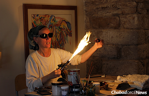 Artisan Sheva Chaya shows her work to the group, including a glass-blowing demonstration.
