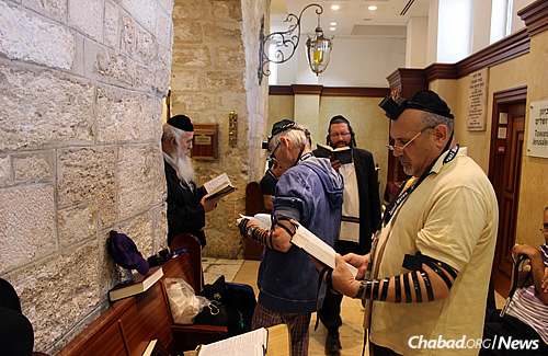 Time for prayer: Eric Suris and his father-in-law, Marvin Berman, in the background