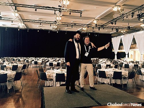Rabbi Yehuda Teichtal, rabbi of the Berlin Jewish community and the head of Chabad of Berlin, with Robby Rjber, vice president of Maccabi in Germany, in front of the table setup before the record-breaking Shabbat dinner in Berlin