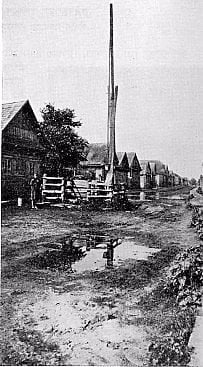 A typical shtetl street - this one is in David Horodok, Belarus - picturing the town well/water pump