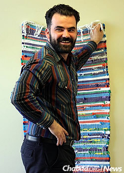 Instructor Brian Kavanaugh hangs a tapestry woven at the center.