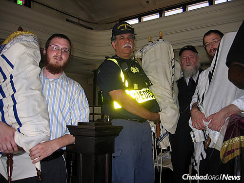 Druk, left, and Shmotkin, right, work with others to evacuate Torahs and religious materials, with Rabbi Gluck and other officials.