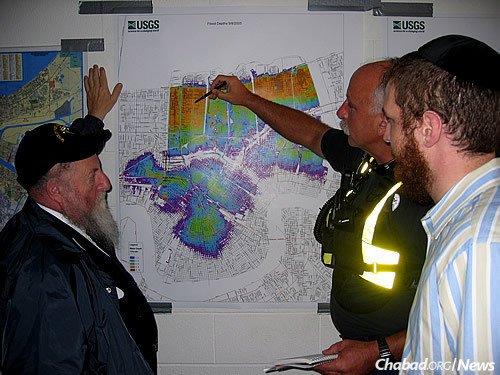 Rabbinical student Mendel Druk, right, and Rabbi Chaim Baruch Gluck, left, observe the mapping out of search-and-rescue routes in Louisiana following Hurricane Katrina.