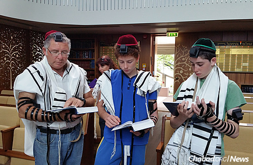 Wrapping tefillin in synagogue. The Jewish community in Estonia is getting ready for what has become a growing tradition there—participating in Tashlich, where in this case, Jews will symbolically cast their sins into the Baltic Sea.