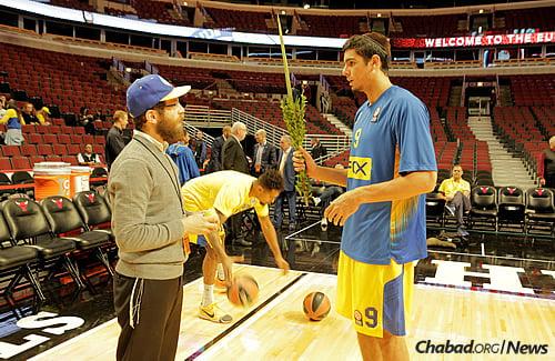 Rabbi Avraham Kagan, co-director of Chabad of River North and Fulton Market, gives a lulav and etrog to Maccabi player Itay Segev. (Photo: Yakov Studio)