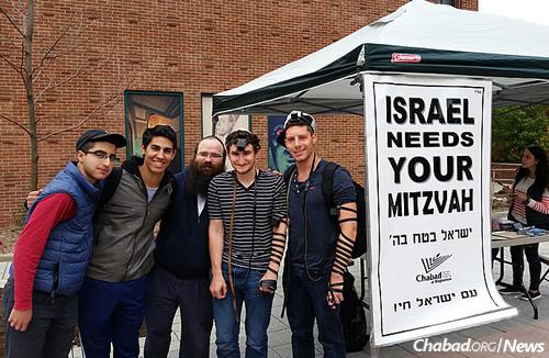 The sign speaks volumes: Binghamton University students with Rabbi Zalman Chein of the Chabad center. (Photo: Chabad of Binghamton)