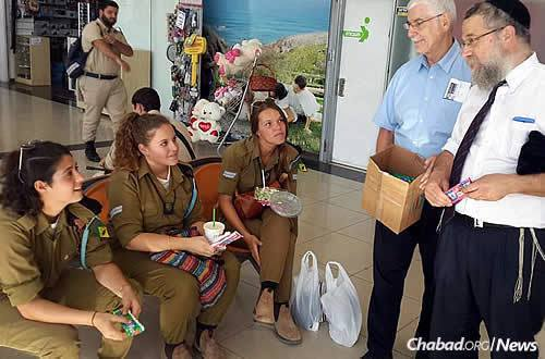Rabbi Sholom Raichik, right, director of Chabad of Upper Montgomery County in Gaithersburg, Md.,and community member Bernard Schack bring gifts for Israeli soldiers in Be'er Sheva, where a deadly attack occurred last week at the central bus station.