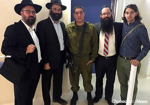 Rabbis Kutner, Chein and Naftalin, along with Brandeis student Miller, stand outside the room where a terrorist is currently being treated, just a few rooms away from where the people he attempted to murder are being cared for. Pictured with them is the soldier guarding the room.
