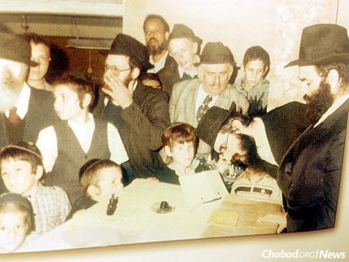 From left: Torah scribe Shalom Michaelashvili, Rabbi Yitzchak Goldberg of Migdal Haemek (bending over the Sefer Torah)
