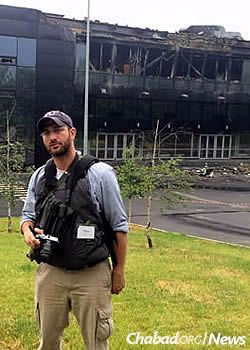 Sam Sokol in Donetsk with the ruins of the city's ruined sports center behind him.