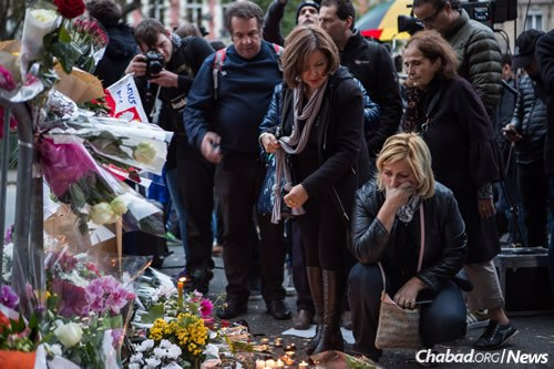 People place flowers and light candles in tribute to the victims of the Paris terror attacks close to the Bataclan theater in the 11th district of Paris. (Photo: Laurence Geai/Flash90)