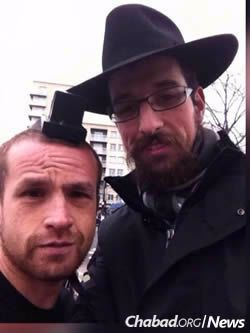 Rabbi Moshe Cohen helps a man don tefillin in January, following the attack on the Hyper Cacher kosher supermarket. Chabad representatives offered tefillin to Jewish men who filed into the streets this Sunday after multiple terrorist attacks throughout Paris.