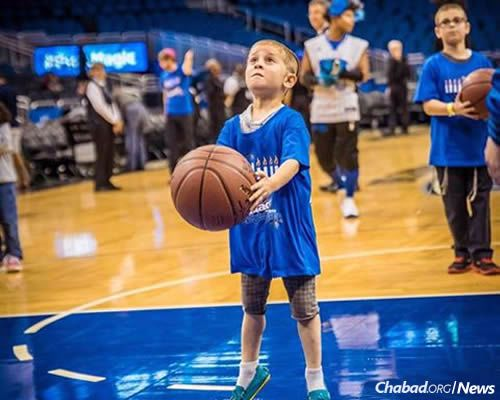 Kids enjoyed watching the Magic play the Celtics on Sunday as part of pre-Chanukah festivities organized by Chabad of Greater Orlando in Maitland, Fla. They also got the chance to make some baskets. (Photo: Michael Fried, www.sonacityphotography.com)