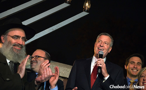New York City Mayor Bill de Blasio, right, joins in the added second-night Chanukah menorah-lighting on Monday as a direct response to a vandalized menorah set up in Carl Schurz Park near Gracie Mansion. Rabbi Ben Tzion Krasnianski, executive director of Chabad Lubavitch of the Upper East Side, is at the far left; in the center is Rabbi Elie Weinstock of Congregation Kehilath Jeshurun. (Mayor's Office Photo/Ed Reed)