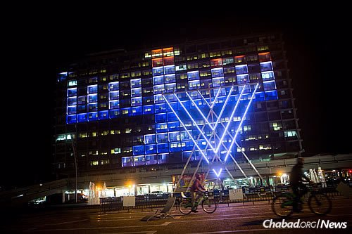 Israelis ride bicycles past a lit-up menorah displayed on the Tel Aviv municipality building. (Photo: Miriam Alster/Flash90)
