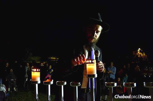 """The recently established Chabad on the Coast, co-directed by Rabbi Eliyahu (""""Eli') and Shterna Sara Naiditch, held its very first public menorah-lighting on Sunday at a park overlooking the Tel Aviv promenade and the Mediterranean Sea. Here, the rabbi leads the event, which was attended by nearly 200 people. (Photo: Chabad on the Coast)"""