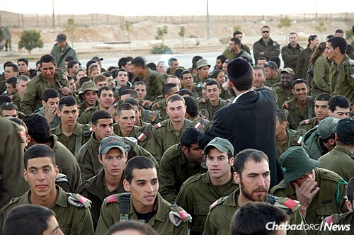 """""""We have 15,000 soldiers at different bases in the Arava desert region, and we visit all of them,"""" says Rabbi Mendi Klein, director of Chabad of Eilat. His wife, Chana Klein, adds that they also hold sizable Chanukah menorah-lightings and events for local residents and the throngs of tourists there. (Photo: Chabad of Eilat)"""