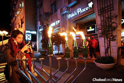 A young woman snaps a photo of a menorah made from glass beer bottles outside of a popular bar in central Jerusalem. (Photo: Mendy Hechtman/Flash90)