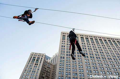 Kids and other attendees of the downtown Chanukah event last Sunday ride on the 300-foot zip line.