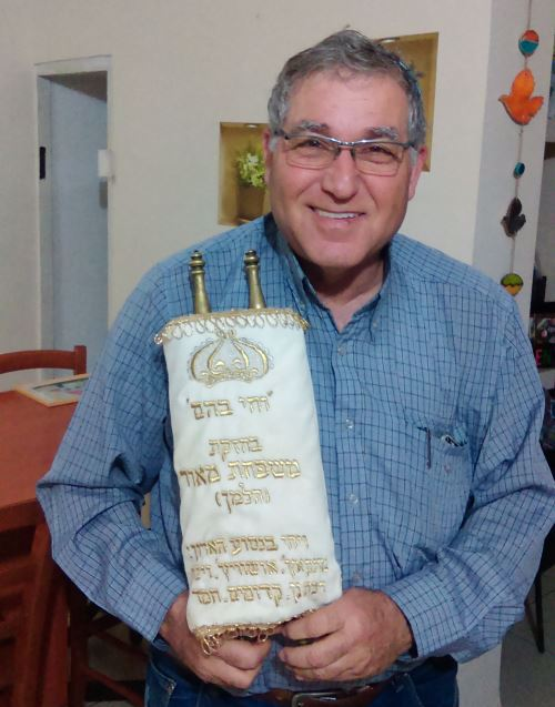 Yaakov Maor with the family Torah scroll smuggled into Auschwitz that he identified by its unusual copper staves.