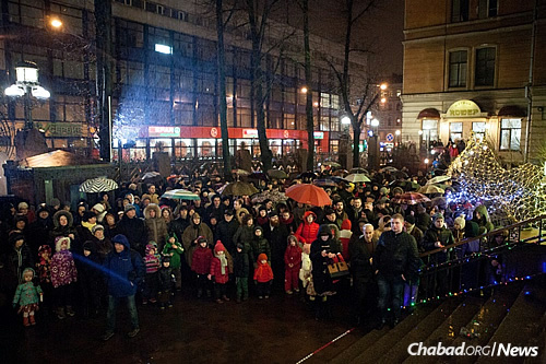 A crowd gathers in the rain to watch the public lighting of a giant menorah in St. Petersburg.