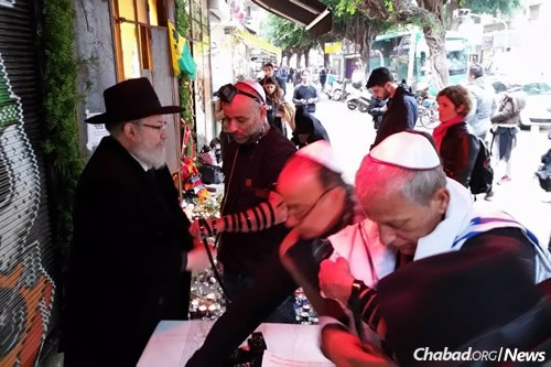 Rabbi Yosef Shmuel Gerlitzky, left, executive director of Chabad in Tel Aviv, has been providing comfort and a chance for Jews to respond in a positive way following Friday's shooting. (Photos: Chabad of Tel Aviv)