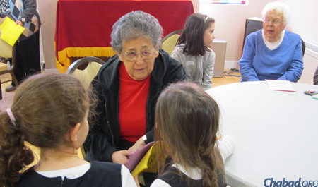 Children also participate in the special day with Torah study and good deeds, like these girls visiting a senior cienter in Montreal. (File photo)