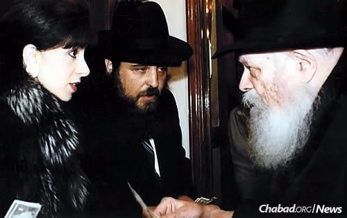 The Rebbe gives a dollar and a blessing to Gordon and his wife, Deborah.