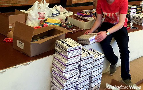 Rabbi Lipsker has been working with a local 18-year-old, who has been attending weekly Shabbat dinners for the past six months and doing well with recovery. Here, he helps organize mishloach manot (gifts of food) for Purim. (Used with permission)