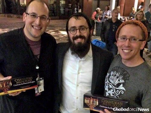 Rabbi Teldon gives menorah kits to Jeremy Rosen, left, and Aaron Horning, right.