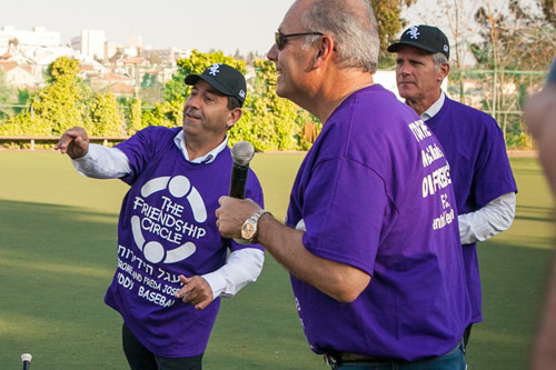 Rami Levy throws out the first ball as Dean Klassman and MK Michael Oren look on.