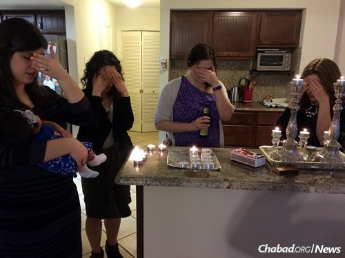 From left: Esther Ansari, Isadora Sintes, Alicia Bach and Rochel Teldon light Shabbat candles at the Teldon home before a YSJA Shabbat dinner in honor of the birth of Esther's daughter.