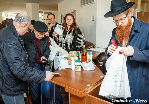 """Distributing kosher-for-Passover items at the """"Matan BeSeiser Fund of Moscow,"""" which provides food for the Jewish needy and for those with large families."""