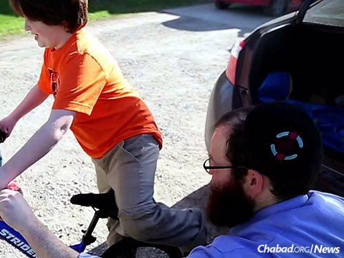 """Rabbi Tzvi Schectman, family coordinator at the Friendship Circle in Michigan, delivers a bike to a child after last year's annual """"Great Bike Giveaway"""" national contest."""
