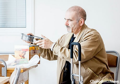 A man takes out a pre-packaged cake and other items for Passover.