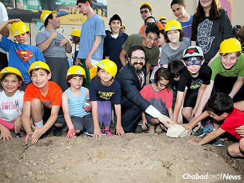 Rabbi Zalman Grossbaum, director of Friendship Circle of MetroWest New Jersey with his wife, Toba, helps lay the cornerstone of the building, assisted by children from the community.
