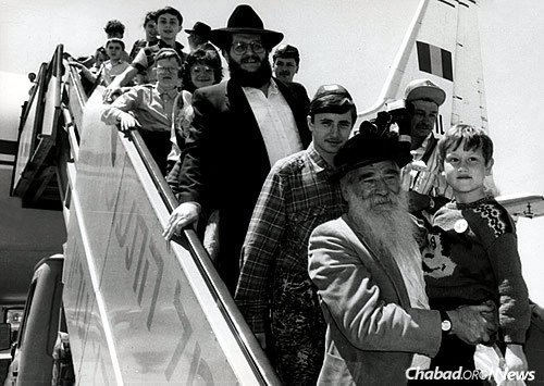 Jewish children affected by the Chernobyl reactor disembark from the Tarom Romanian airplane in Tel Aviv. Holding a child in the front is Shlomo Maidanchik, a Chabad activist in Israel who served for many years as mayor of Kfar Chabad. Behind him is Aronov.