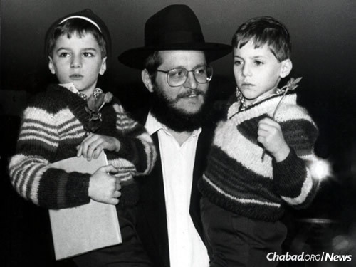 Rabbi Josef Aronov, chairman of Chabad in Israel, holds two recently arrived children.