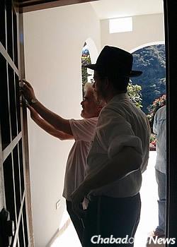Helping a resident hang a mezuzah.